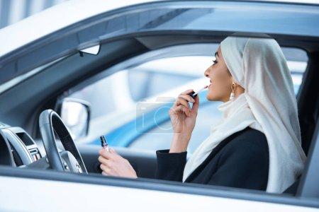 Photo pour Jeune femme musulmane assis dans la voiture et se maquiller - image libre de droit