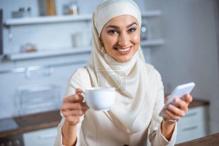 Photo pour Souriante jeune femme musulmane tenant la tasse de café et de smartphone à la maison - image libre de droit
