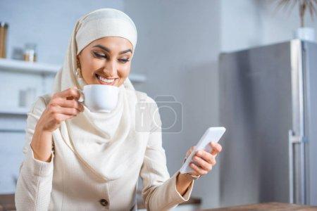Photo pour Sourire de femme musulmane tenue tasse de café et à l'aide de smartphone à la maison - image libre de droit