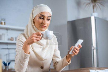 Photo pour Jeune femme musulmane tenant une tasse de café et utilisant un smartphone à la maison - image libre de droit