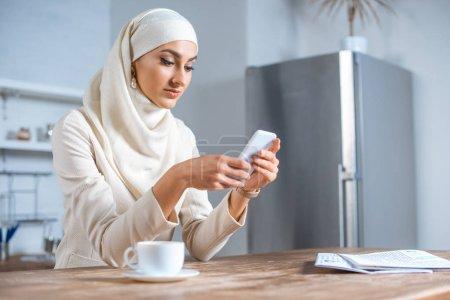 Photo pour Belle jeune femme musulmane avec le smartphone à la maison - image libre de droit