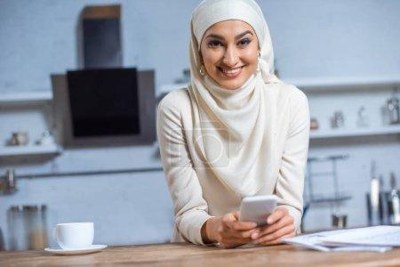 Photo pour Belle jeune femme musulmane à l'aide de smartphone et souriant à la caméra - image libre de droit