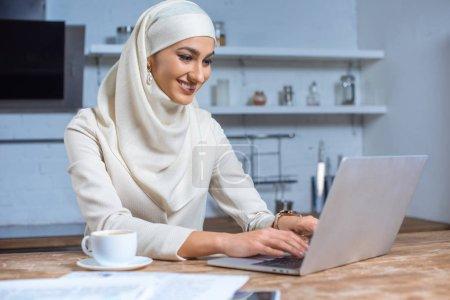Photo pour Belle souriante jeune femme musulmane avec ordinateur portable à la maison - image libre de droit