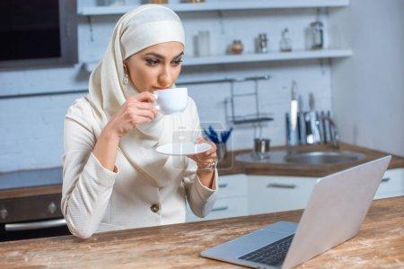 Photo pour Jeune femme musulmane, boire du café et à l'aide d'ordinateur portable à la maison - image libre de droit