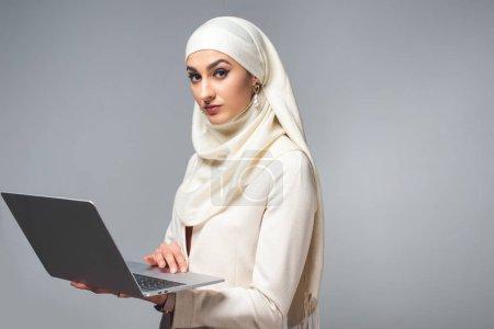 Photo pour Jeune femme musulmane à l'aide d'ordinateur portable et regardant la caméra isolée sur fond gris - image libre de droit