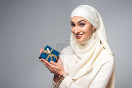 happy young young muslim woman holding present and smiling at camera isolated on grey