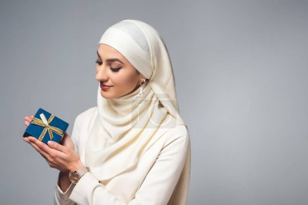 smiling young young muslim woman holding present isolated on grey