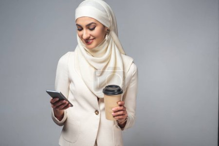 smiling young muslim woman holding coffee to go and using smartphone isolated on grey