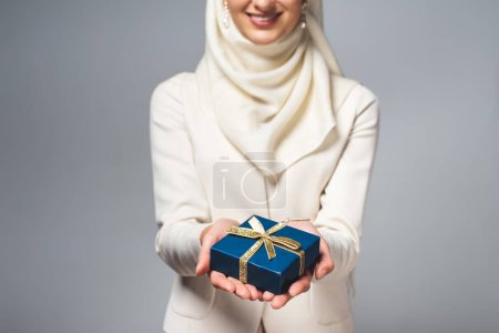 cropped shot of smiling young muslim woman holding gift box isolated on grey