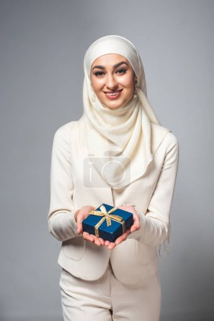 happy young muslim woman holding gift box and smiling at camera isolated on grey
