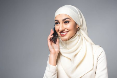 beautiful happy young muslim woman talking by smartphone and looking away isolated on grey