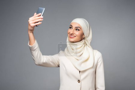 beautiful smiling muslim woman taking selfie with smartphone isolated on grey