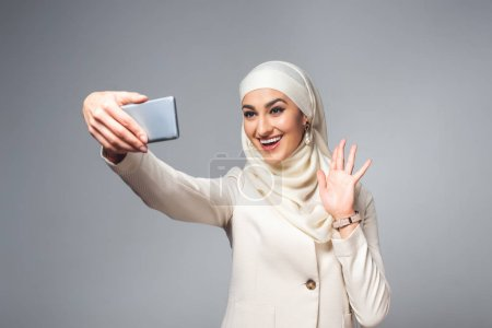 happy young muslim woman taking selfie with smartphone isolated on grey