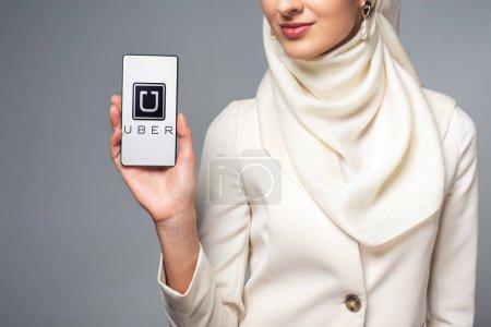Photo pour Plan recadré de femme musulmane souriante tenant smartphone avec application uber isolé sur gris - image libre de droit