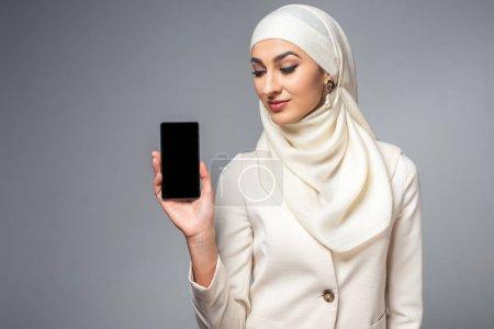 Photo pour Belle jeune femme musulmane souriante tenant smartphone avec écran blanc isolé sur gris - image libre de droit