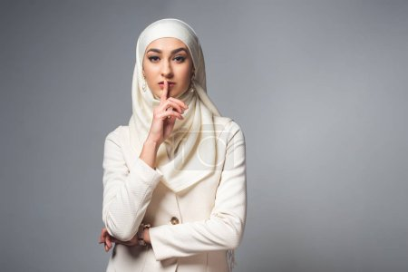 young muslim woman standing with finger on lips and looking at camera isolated on grey