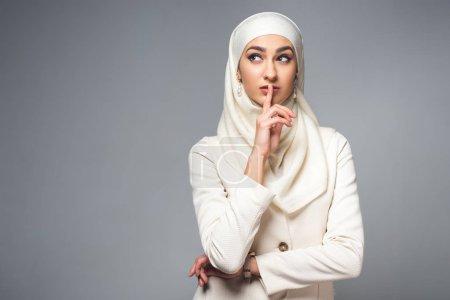 Photo pour Jeune femme musulmane permanent avec le doigt sur les lèvres et à la recherche de suite isolé sur fond gris - image libre de droit