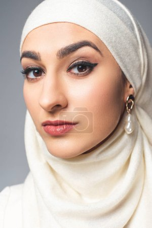 portrait of beautiful young muslim woman looking at camera isolated on grey