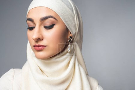 close-up portrait of beautiful young muslim woman looking down isolated on grey