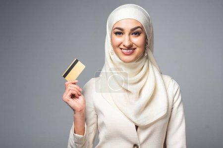 Photo pour Belle femme musulmane tenant carte de crédit et souriant à la caméra isolée sur gris - image libre de droit