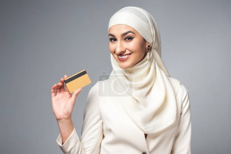 young muslim woman holding credit card and smiling at camera isolated on grey