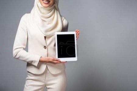 Photo pour Photo recadrée de femme musulmane souriante tenant la tablette numérique avec écran blanc isolé sur fond gris - image libre de droit