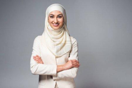 Photo pour Portrait de belle jeune femme musulmane debout avec les bras croisés et souriant à la caméra isolée sur gris - image libre de droit