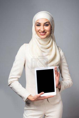 Photo pour Jeune femme musulmane tenant une tablette numérique avec écran blanc et souriant à la caméra isolée sur fond gris - image libre de droit