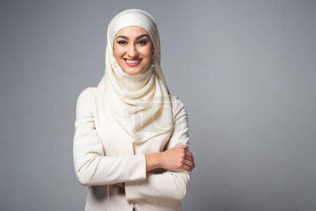 Photo pour Jeune femme musulmane debout avec les bras croisés et souriant à la caméra isolée sur gris - image libre de droit