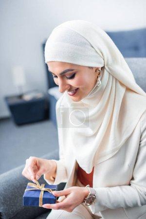 Photo pour Heureuse jeune femme musulmane, ouverture de boîte de cadeau à la maison - image libre de droit