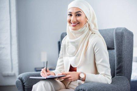Photo pour Belle jeune femme musulmane écrit dans un cahier et souriant à la caméra - image libre de droit