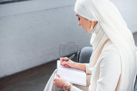Photo pour Vue d'angle élevé de jeune femme musulmane écrire dans cahier à la maison - image libre de droit