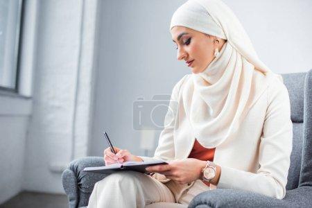 Photo pour Belle jeune femme musulmane assis dans le fauteuil et l'écriture de bloc-notes - image libre de droit