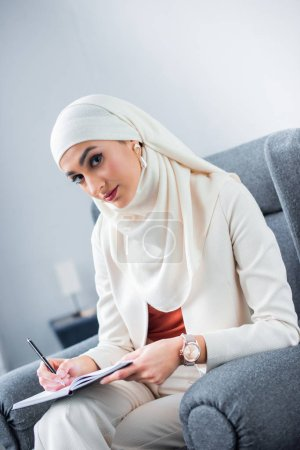 Photo pour Jeune femme musulmane écrire dans cahier et regardant la caméra - image libre de droit