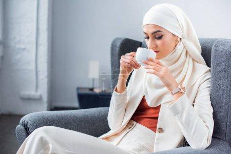 Photo pour Jeune femme musulmane, boire du café à la maison - image libre de droit