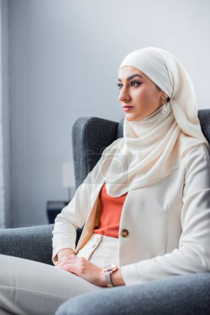 Photo for Pensive young muslim woman sitting in chair and looking away - Royalty Free Image