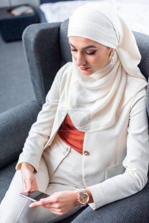 Photo pour Belle jeune femme musulmane assis dans le fauteuil et l'utilisation de smartphone - image libre de droit