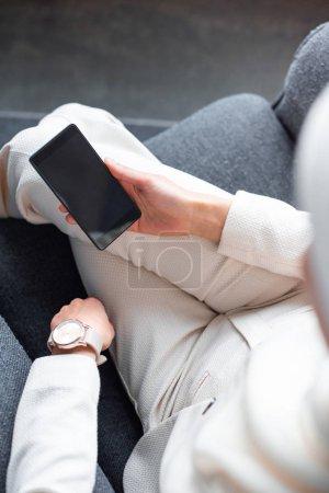 Photo pour Recadrée coup de la femme musulmane à l'aide de smartphone avec un écran blanc à la maison - image libre de droit