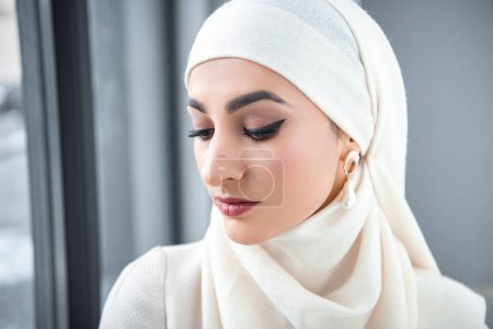 portrait of beautiful pensive young muslim woman looking down