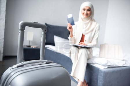 Photo for Close-up view of suitcase and smiling muslim woman holding passport with boarding pass at home - Royalty Free Image