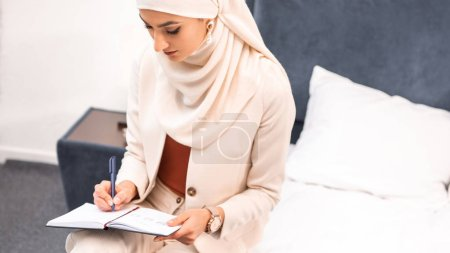 Photo pour Vue grand angle de la jeune femme musulmane assise sur le lit et écrivant dans un cahier - image libre de droit