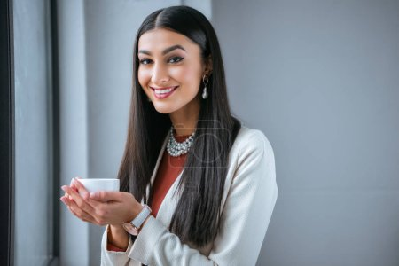 Photo for Beautiful young woman holding cup of coffee and smiling at camera - Royalty Free Image