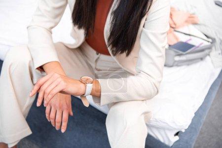 Photo pour Recadrée tir d'élégante jeune femme en costume blanc élégant, assis sur le lit - image libre de droit