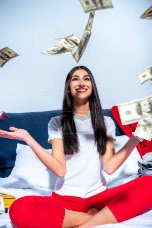 cheerful young brunette woman sitting on bed and throwing dollar banknotes