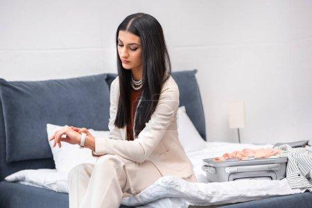 Photo pour Élégante fille brune en costume blanc élégant assis sur le lit avec valise et vérifier la montre-bracelet - image libre de droit