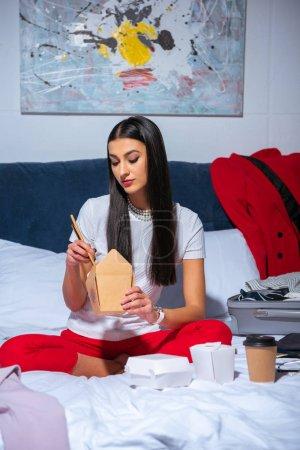 Photo pour Jeune femme brune assise sur le lit et manger de la nourriture asiatique - image libre de droit