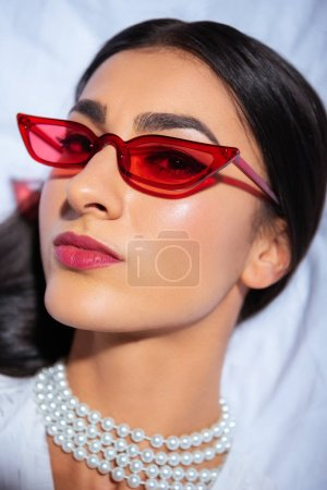 close-up portrait of beautiful young woman in red eyeglasses looking at camera