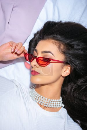 Photo for Top view of elegant brunette woman lying on bed and adjusting red eyeglasses - Royalty Free Image