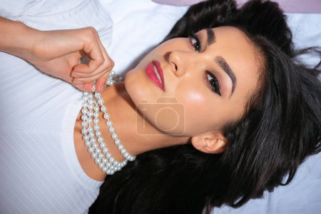 beautiful woman in pearl necklace lying on bed and looking at camera