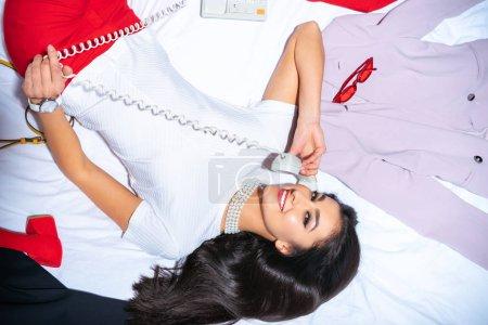 Photo pour Vue de dessus de belle jeune femme souriant à la caméra tout en se trouvant sur le lit et parler par téléphone - image libre de droit